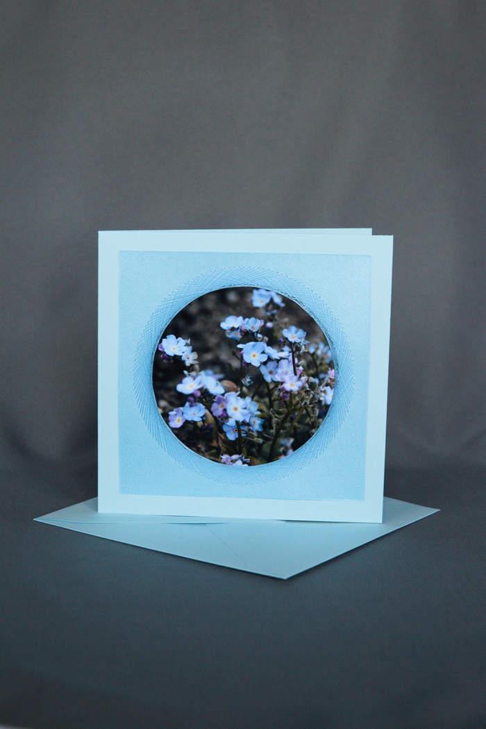 Hellblaue Vergissmeinnicht umrahmt von gesticktem Kranz auf Geburtstagskarte